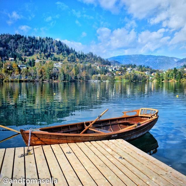 barca a remi ormeggiata sul lago di bled con collina e riflessi sul lago